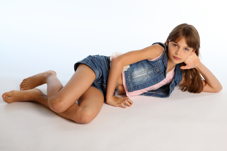 Beautiful girl in a denim shorts is resting on the floor barefoot. Elegant attractive child with a slender body and bare long legs. The young schoolgirl is 9 years old. Banco de Imagens