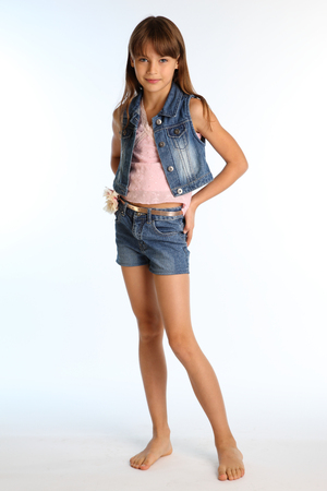 Beautiful girl in a denim shorts is standing barefoot at full length. Elegant attractive child with a slender body and bare long legs. The young schoolgirl is 9 years old.