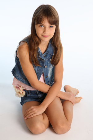 Beautiful girl in a denim shorts is resting on the floor barefoot. Elegant attractive child with a slender body and bare long legs. The young schoolgirl is 9 years old. Stock Photo