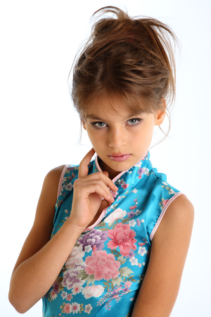 Portrait with hand of a beautiful girl in an asian blue dress. The young attractive child 9 years old in fashion style.