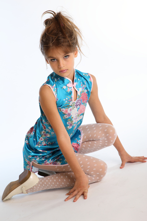 Beautiful girl in an asian blue dress is sitting on a white background. Elegant attractive child with a slender body and long legs in white pantyhose. The young model 9 years old in fashion style. Фото со стока - 100740776