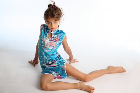 Beautiful girl in an asian blue dress is sitting barefoot. Elegant attractive child with a slender body and bare long legs. The young model 9 years old in fashion style.