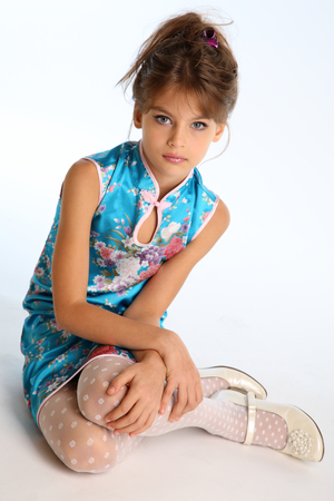 Beautiful girl in an asian blue dress is sitting on a white background. Elegant attractive child with a slender body and long legs in white pantyhose. The young model 9 years old in fashion style. Zdjęcie Seryjne - 100778992
