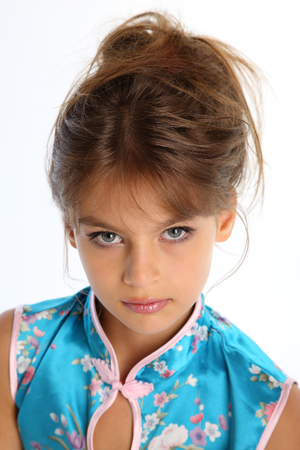 Close-up portrait of a beautiful girl in an asian blue dress. The young attractive child 9 years old in fashion style. Stockfoto