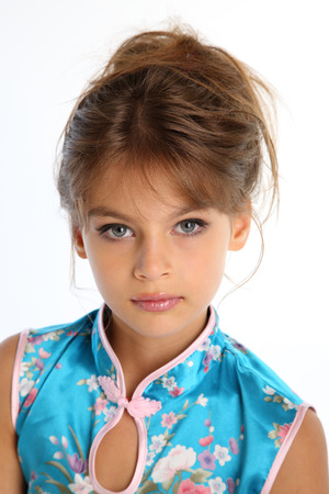 Close-up portrait of a beautiful girl in an asian blue dress. The young attractive child 9 years old in fashion style. Stock Photo