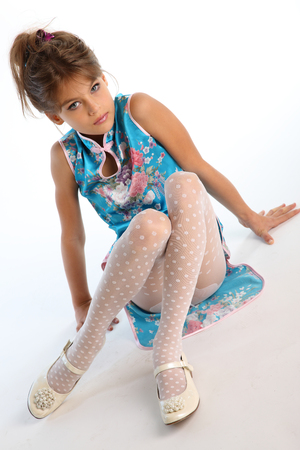 Beautiful girl in an asian blue dress is sitting on a white background. Elegant attractive child with a slender body and long legs in white pantyhose. The young model 9 years old in fashion style.