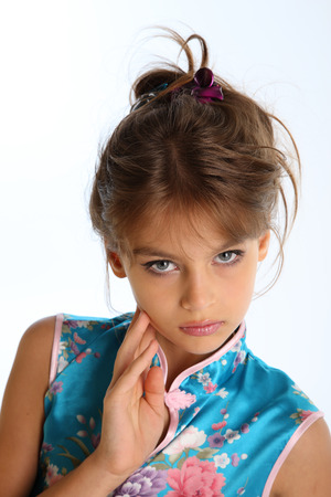 Close-up portrait of a beautiful girl in an asian blue dress. The young attractive child 9 years old in fashion style. Banque d'images