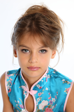 Close-up portrait of a beautiful girl in an asian blue dress. The young attractive child 9 years old in fashion style. Foto de archivo