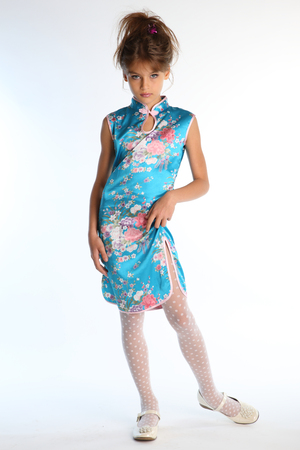 Beautiful girl in an asian blue dress is standing on a white background. Elegant attractive child with a slender body and long legs in white pantyhose. The young model 9 years old in fashion style.