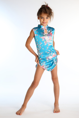 Beautiful girl in an asian blue dress is standing barefoot. Elegant attractive child with a slender body and bare long legs. The young model 9 years old in fashion style.