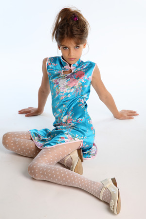 Beautiful girl in an asian blue dress is sitting on a white background. Elegant attractive child with a slender body and long legs in white pantyhose. The young model 9 years old in fashion style. Zdjęcie Seryjne - 100778996