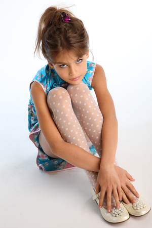 Beautiful girl in an asian blue dress is sitting on a white background. Elegant attractive child with a slender body and long legs in white pantyhose. The young model 9 years old in fashion style. Zdjęcie Seryjne - 100778655