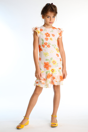 Tanned little girl in a bright summer dress is standing on white background. Attractive child with a slender body and long bare legs in yellow shoes. The young model 9 years old in fashion style.