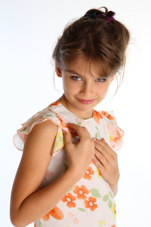 Portrait of beautiful tanned little girl in a bright summer dress on white background. Elegant attractive child-model 9 years old in fashion style. Stok Fotoğraf