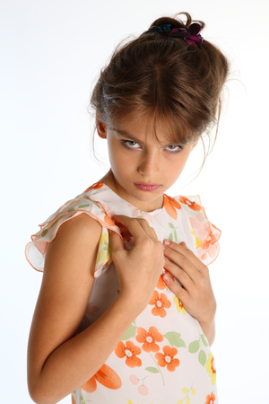 Portrait of beautiful tanned little girl in a bright summer dress on white background. Elegant attractive child-model 9 years old in fashion style. Banque d'images