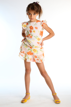 Tanned little girl in a bright summer dress is standing on white background. Attractive child with a slender body and long bare legs in yellow shoes. The young model 9 years old in fashion style. Reklamní fotografie - 101215832