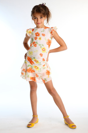 Happy little girl in a bright summer dress is standing on white background. Attractive child with a slender body and long bare legs in yellow shoes. The young model 9 years old in fashion style. Stock Photo