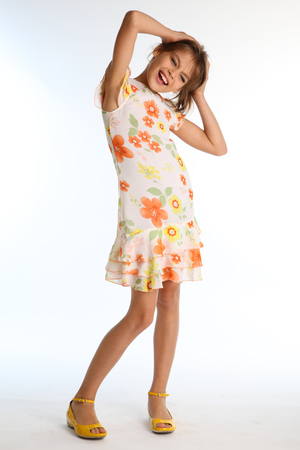 Emotional little girl in a bright summer dress is standing on white background. Attractive child with a slender body and long bare legs in yellow shoes. The young model 9 years old in fashion style. Stock Photo