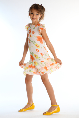 Happy little girl in a bright summer dress is standing on white background. Attractive child with a slender body and long bare legs in yellow shoes. The young model 9 years old in fashion style. Banque d'images