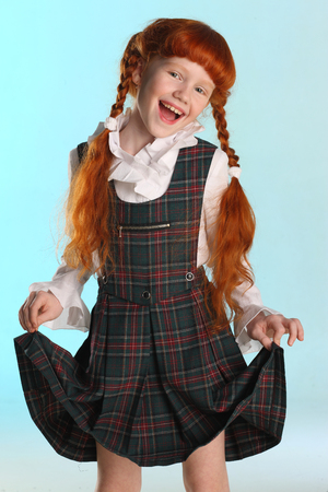 Portrait of beautiful happy little redhead girl shows her school uniform. Elegant attractive child-model with a slender body and slim bare legs. The young schoolgirl is 8 years old.