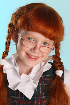 Close-up portrait of beautiful little redhead girl in a school uniform. Pretty attractive child posing with glasses artistically. The young schoolgirl is 8 years old.