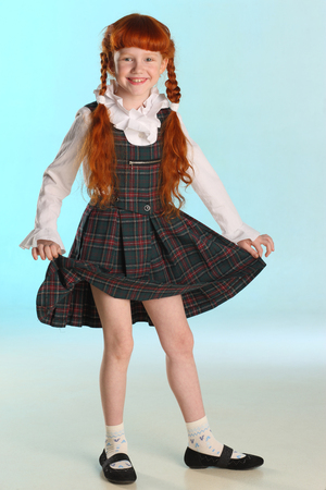 Beautiful happy little redhead girl shows her school uniform at full length. Elegant attractive child with a slender body and slim bare legs. The young schoolgirl is 8 years old. 免版税图像