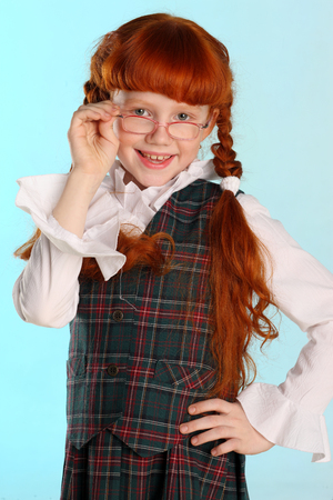 Portrait of beautiful little redhead girl is standing in a school uniform. Pretty attractive child poses with glasses artistically. The young schoolgirl is 8 years old. Stockfoto - 101361480