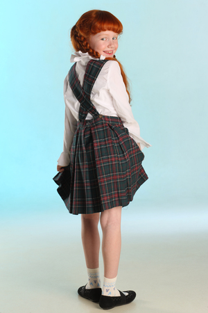 Beautiful happy little redhead girl shows her school uniform at full length. Elegant attractive child with a slender body and slim bare legs. The young schoolgirl is 8 years old. Stock Photo