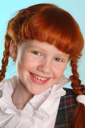 Close-up portrait of beautiful happy little redhead girl in a school uniform. Pretty attractive child poses artistically. The young schoolgirl is 8 years old.