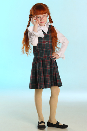 Beautiful little redhead girl in a school uniform is standing at full length. Elegant attractive child with a slender body and slim legs in tights. The young schoolgirl is 8 years old.