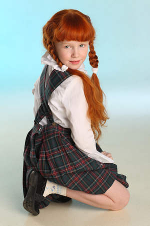 Beautiful little redhead girl in a school uniform posing squatting. Cheerful attractive child with a slender body and slim bare legs. The young schoolgirl is 8 years old. Stockfoto