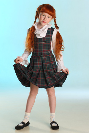 Beautiful happy little redhead girl shows her school uniform at full length. Elegant attractive child with a slender body and slim bare legs. The young schoolgirl is 8 years old. 写真素材 - 101361000