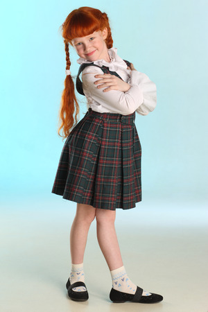 Beautiful happy little redhead girl shows her school uniform at full length. Elegant attractive child with a slender body and slim bare legs. The young schoolgirl is 8 years old. Stockfoto - 101361005