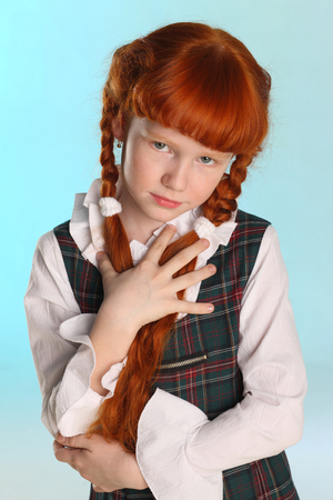 Portrait of beautiful little redhead girl shows her school uniform. Pretty attractive child-model poses artistically. The young schoolgirl is 8 years old.