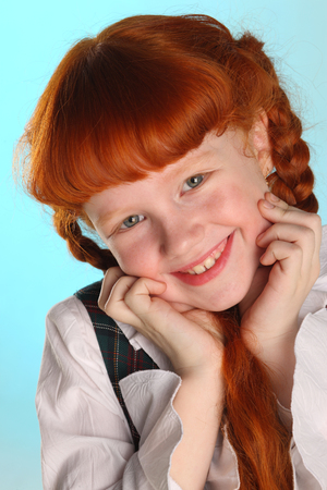 Portrait of beautiful happy little redhead girl in a school uniform. Pretty attractive child poses artistically. The young schoolgirl is 8 years old. Stockfoto