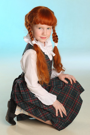 Beautiful little redhead girl in a school uniform posing squatting. Cheerful attractive child with a slender body and slim bare legs. The young schoolgirl is 8 years old. Banque d'images