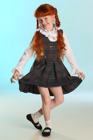 Beautiful happy little redhead girl shows her school uniform at full length. Elegant attractive child with a slender body and slim bare legs. The young schoolgirl is 8 years old. Reklamní fotografie