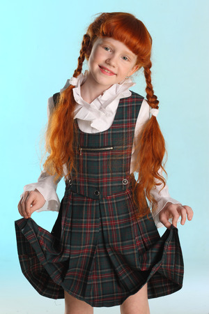 Portrait of beautiful little redhead girl shows her school uniform. Elegant attractive child-model with a slender body and slim bare legs. The young schoolgirl is 8 years old.
