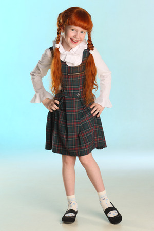 Beautiful happy little redhead girl shows her school uniform at full length. Elegant attractive child with a slender body and slim bare legs. The young schoolgirl is 8 years old. Banque d'images - 101361049