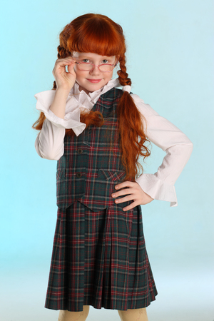 Portrait of beautiful little redhead girl is standing in a school uniform. Pretty attractive child poses with glasses artistically. The young schoolgirl is 8 years old.