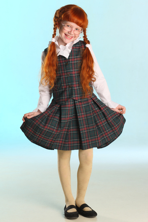 Beautiful happy little redhead girl in a school uniform is standing at full length. Elegant attractive child with a slender body and slim legs in tights. The young schoolgirl is 8 years old.