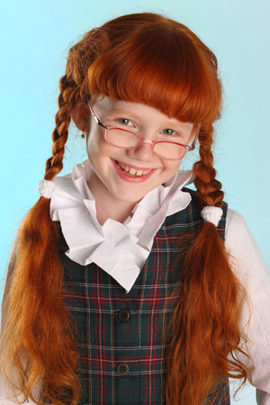 Portrait of beautiful happy little redhead girl is standing in a school uniform. Pretty attractive child poses with glasses artistically. The young schoolgirl is 8 years old.