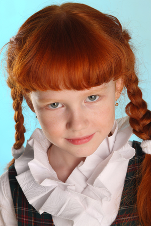 Close-up portrait of beautiful little redhead girl in a school uniform. Pretty attractive child poses artistically. The young schoolgirl is 8 years old.