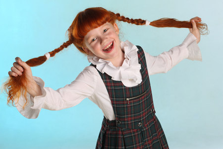 Portrait of beautiful happy little redhead girl shows her long chic hair. Cheerful attractive child-model in a school uniform. The young schoolgirl is 8 years old.