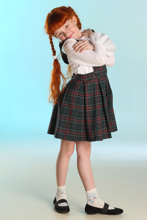 Beautiful happy little redhead girl shows her school uniform at full length. Elegant attractive child with a slender body and slim bare legs. The young schoolgirl is 8 years old. Stockfoto