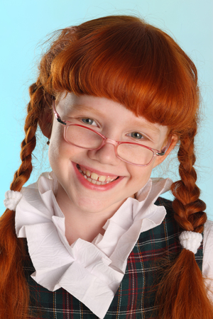 Close-up portrait of happy beautiful little redhead girl in a school uniform. Pretty attractive child posing with glasses artistically. The young schoolgirl is 8 years old.
