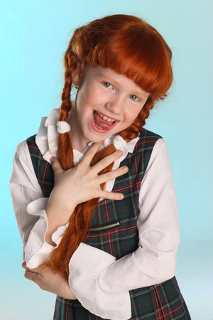 Portrait of beautiful happy little redhead girl shows her pink tongue. Cheerful attractive child-model in a school uniform. The young schoolgirl is 8 years old.