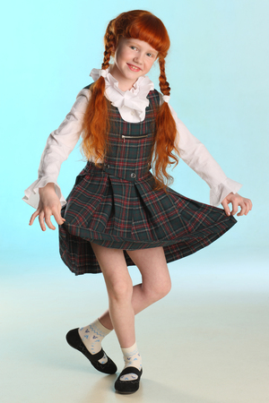Beautiful happy little redhead girl shows her school uniform at full length. Elegant attractive child with a slender body and slim bare legs. The young schoolgirl is 8 years old. Banque d'images
