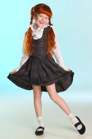 Beautiful happy little redhead girl shows her school uniform at full length. Elegant attractive child with a slender body and slim bare legs. The young schoolgirl is 8 years old. 写真素材
