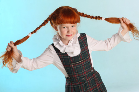 Portrait of beautiful little redhead girl shows her long chic hair. Cheerful attractive child-model in a school uniform. The young schoolgirl is 8 years old. Stockfoto